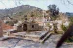 Από την αυλή του Αγίου Αντωνίου κοιτάζοντας προς το Βορρά. Στην κορυφή του λόφου Κάτω Σαβουρέ (στο βάθος) διατηρούνται τα ερείπια ενός από τους πολλούς πύργους (μικρά φρούρια) που είχαν κατασκευάσει οι Τούρκοι για να ελέγχουν το χωριό. Κάτω από τη υδατοδεξαμενή (το κτίσμα, ενετικής τεχνοτροπίας, στο κεντρικό πάνω μέρος της φωτογραφίας) τοποθετούνταν οι στόχοι για το αγώνισμα της σκοποβολής στους αγώνες της «Τρίτης τω Σκολώ» στους Λάκκους.