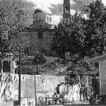 Άνοιξη του 1959. Από την κεντρική πλατεία του χωριού , το «Σελί», με θέα τον Άγιο Αντώνιο. Καθισμένος διακρίνεται ο παππούς του γράφοντα Γεώργιος Χαρ. Κουτρούλης (Πρωτινός), σε ηλικία 36 χρονών, στην αυλή του καφενείου του. Αριστερά και πάνω διακρίνεται το καφενείο του Γεωργίου Ι. Σκουλά.
